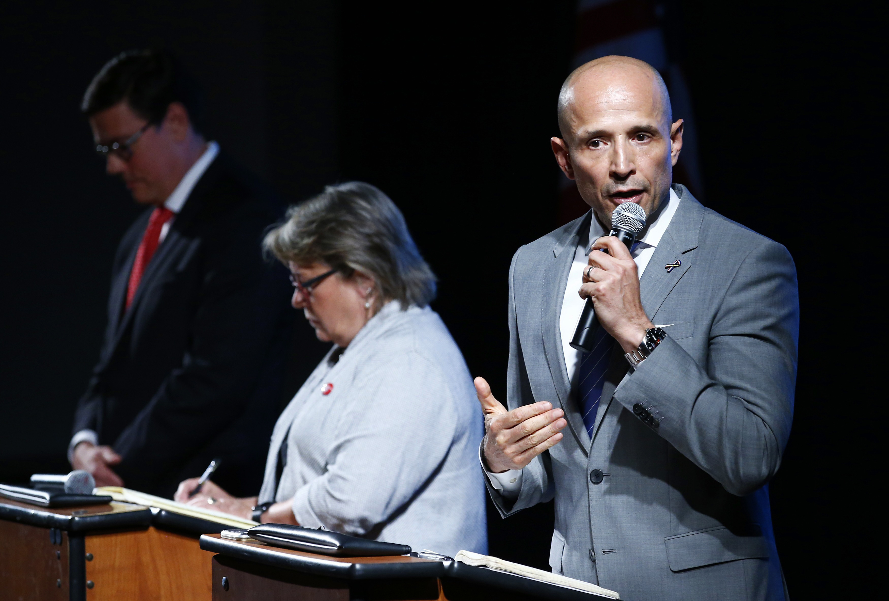 Democratic Arizona gubernatorial candidate David Garcia, right, answers a question as he debates with other candidates.