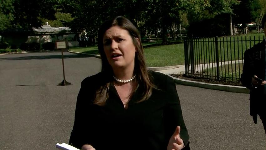 White House press secretary Sarah Sanders speaks to reporters outside the White House.