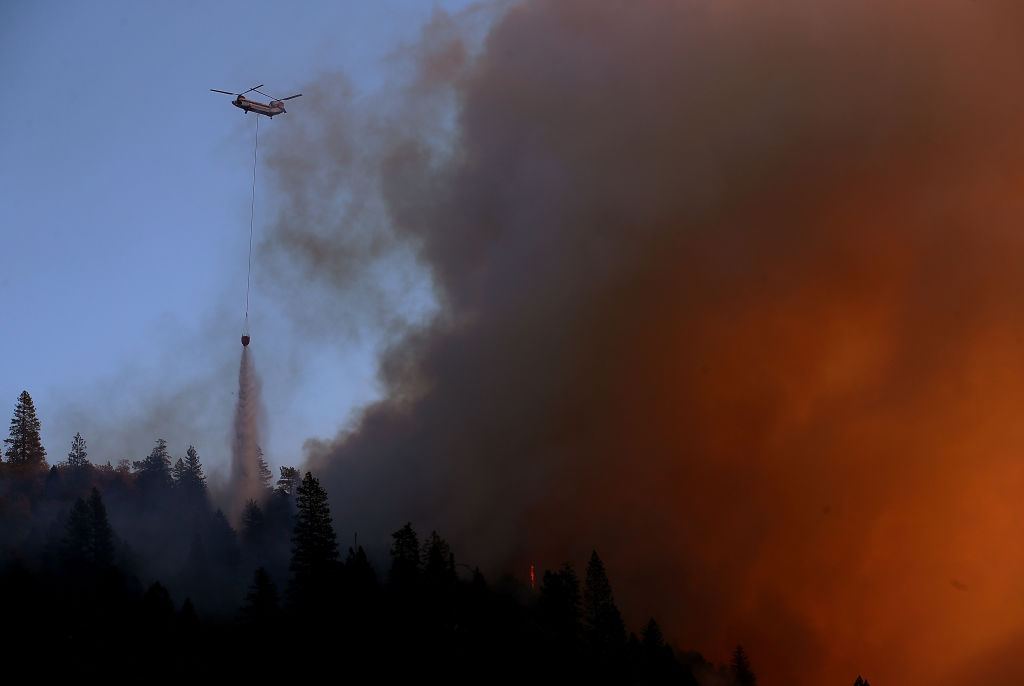 A helicopter drops water on the Camp Fire as it burns in the hills on Nov. 11, 2018 near Cresta, California.