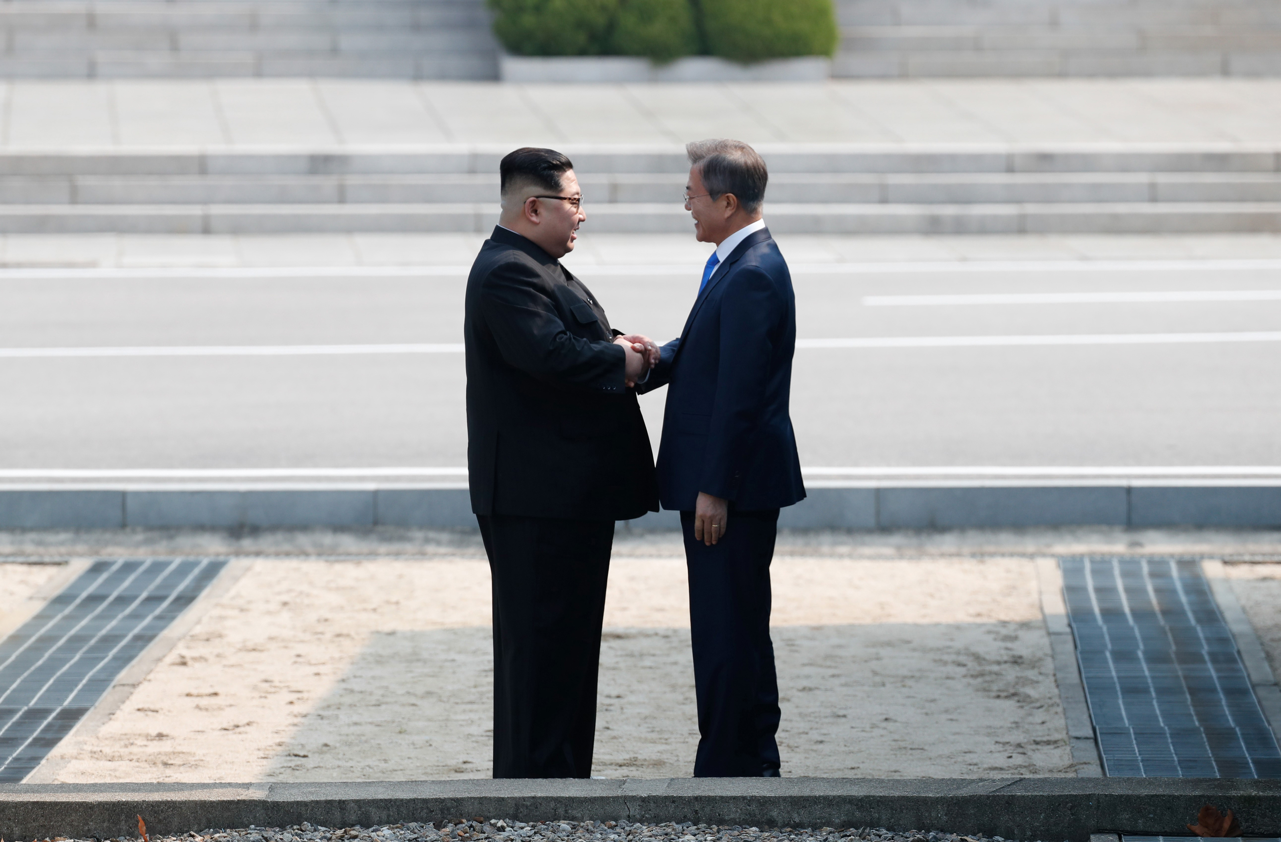 Moon Jae-in and Kim Jong Un shake hands on the southern side of the demilitarized zone after meeting.