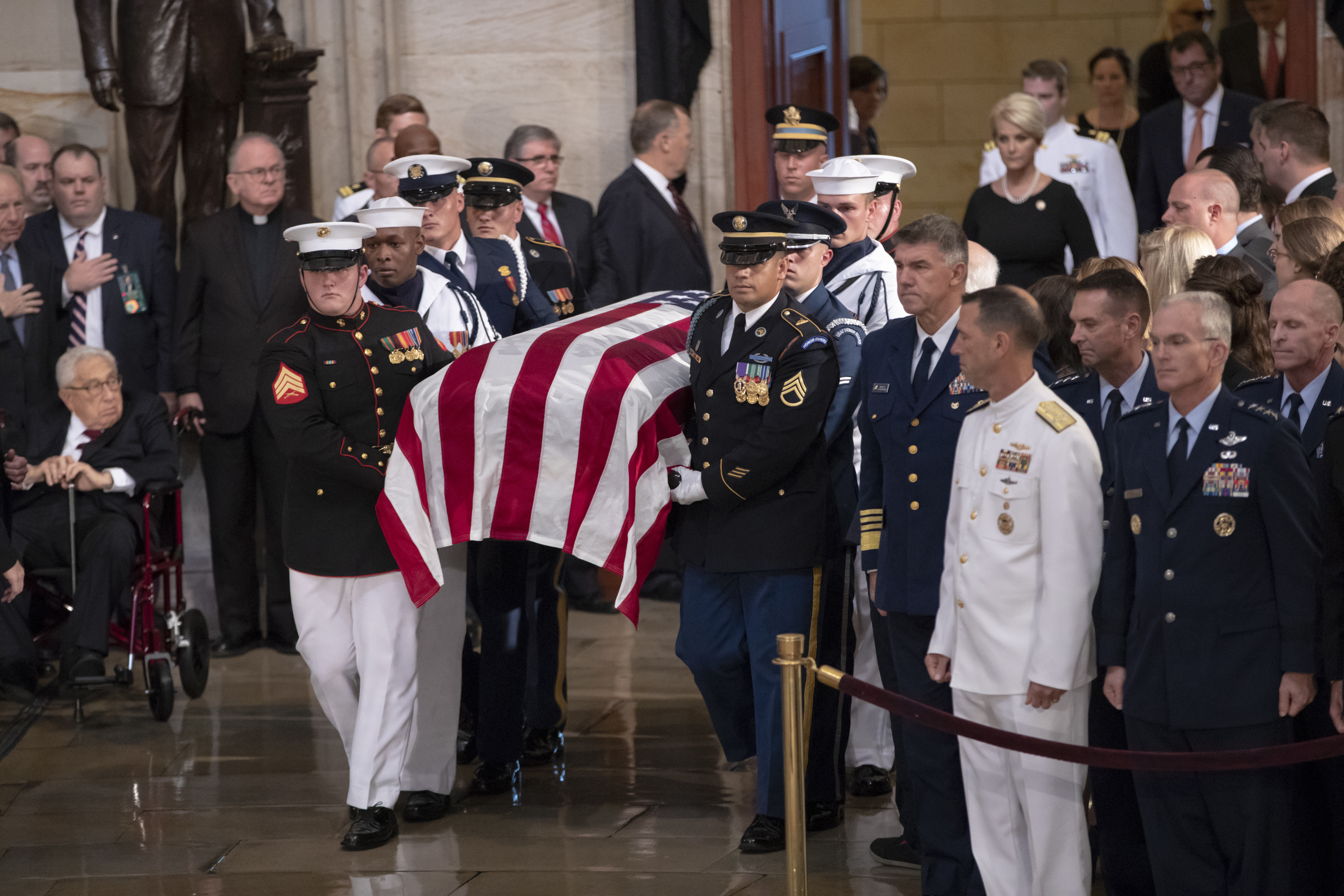 The flag-draped casket bearing the remains of Sen. John McCain of Arizona is carried into the Capitol Rotunda, followed by his widow, Cindy McCain, upper right, for a farewell ceremony and public visitation on Aug. 31, 2018 in Washington.