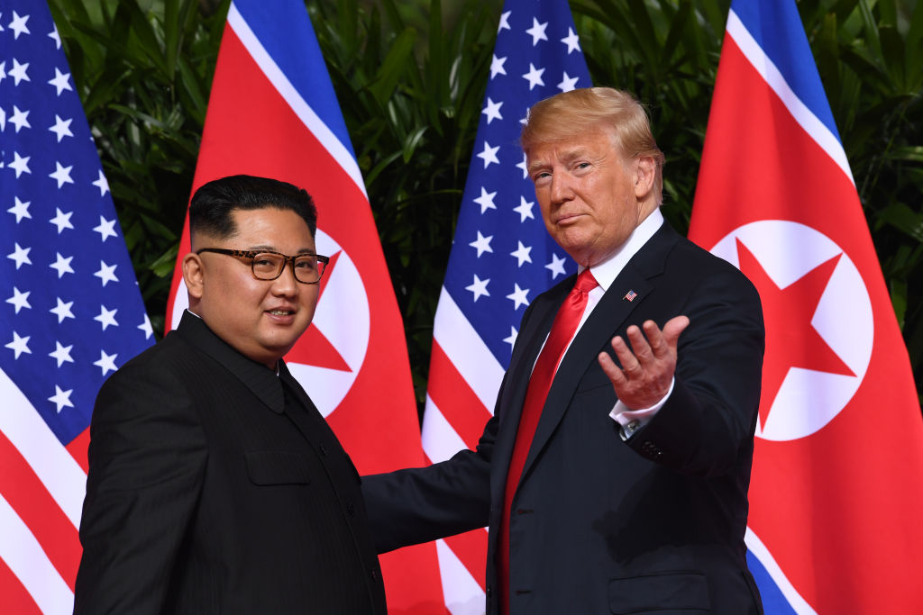 President Trump gestures as he meets with North Korea's leader Kim Jong Un at the start of their historic US-North Korea summit, at the Capella Hotel on Sentosa island in Singapore on June 12, 2018.