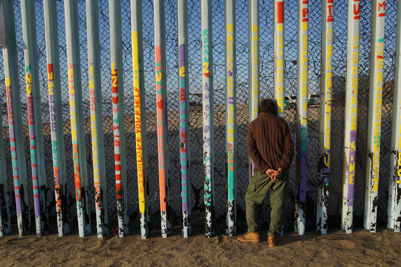 A man looks through the U.S.-Mexico border wall in Tijuana, Mexico, on Sunday.