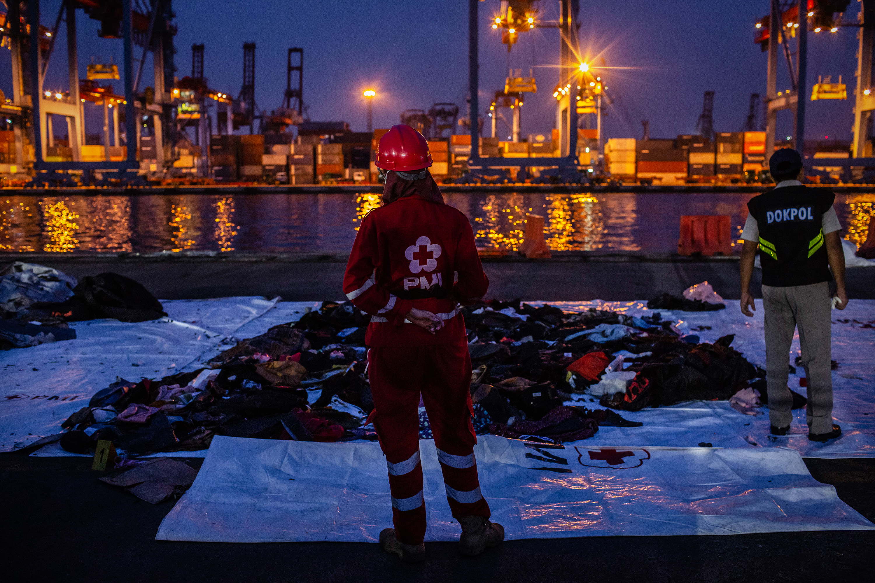 An Indonesian red cross member stands in front of recovered personal items from Lion Air flight JT 610 at the Tanjung Priok port on Tuesday in Jakarta.