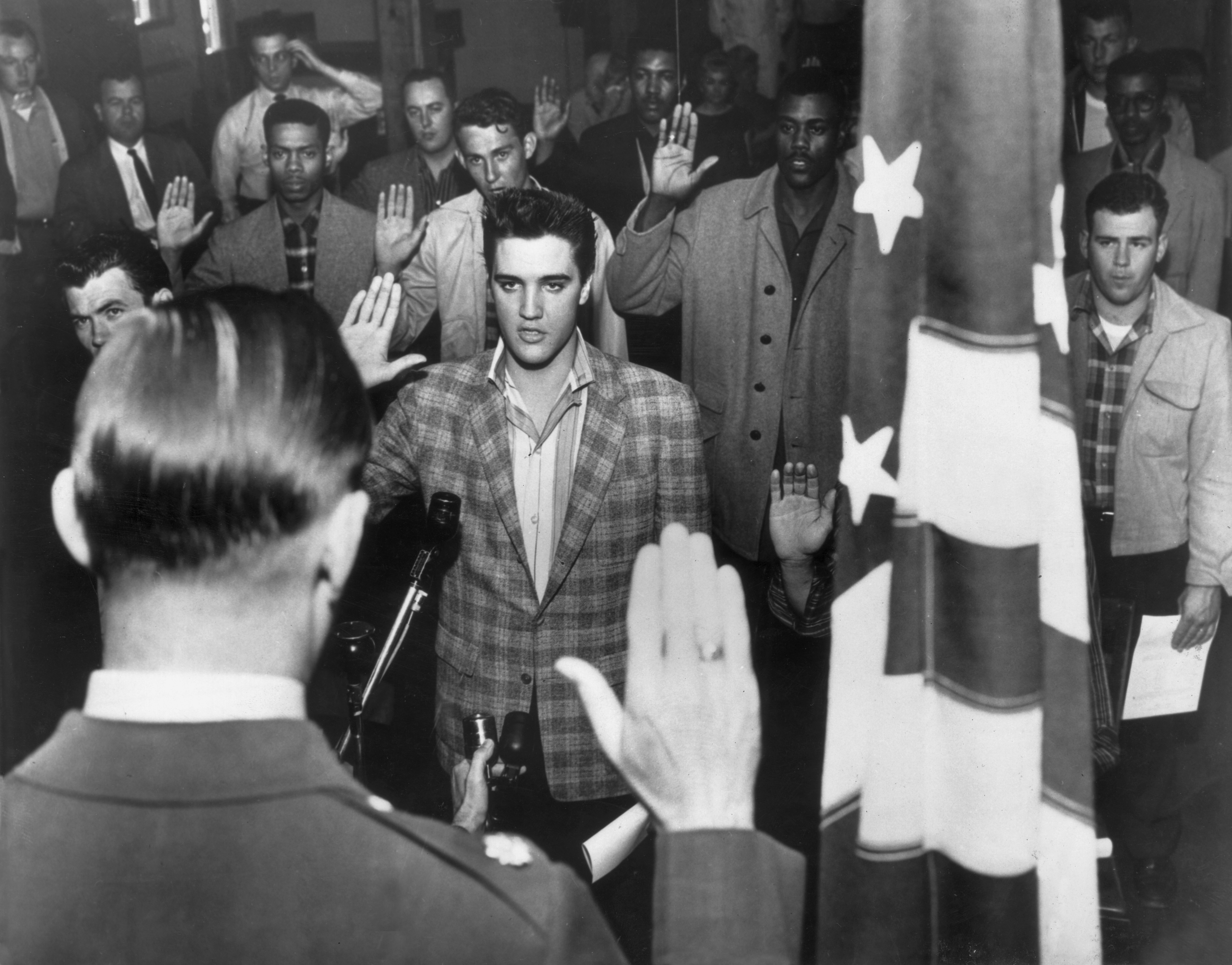 Elvis Presley stands with a group of young men at an induction center, raising their right hands as they are sworn into the United States Army, in 1958.