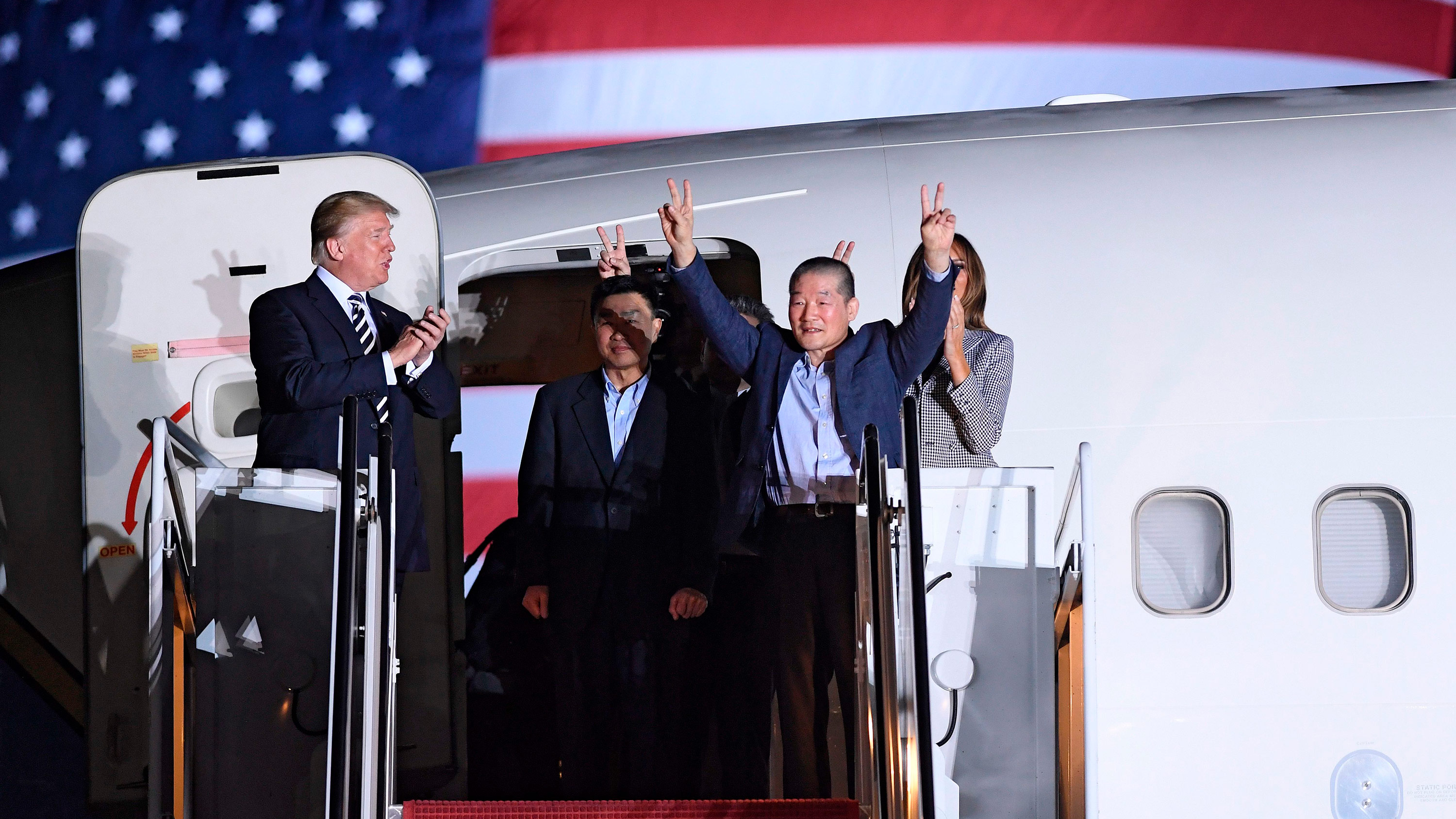 US President Donald Trump (left) applauds as Kim Dong Chul (second right) gestures upon his return with Kim Hak-song (center) and Tony Kim (behind).