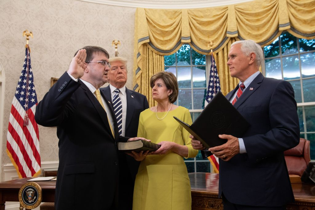 President Donald Trump stands alongside Robert Wilkie (L) and his wife, Julia (2R), as Wilkie is sworn in by US Vice President Mike Pence in the Oval Office of the White House on July 30, 2018.