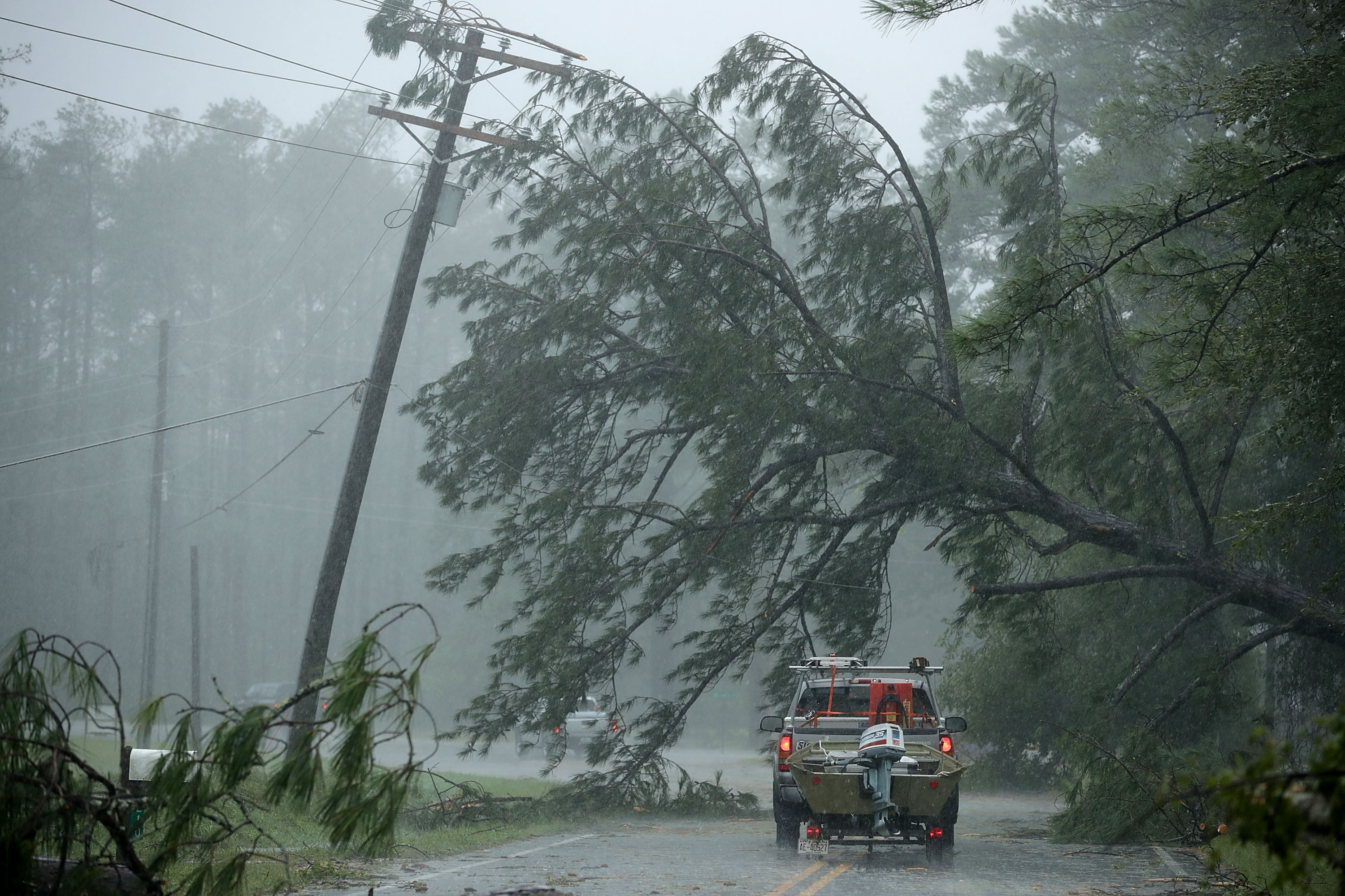 A volunteer rescue truck drives underneath a fallen tree in New Bern, North Carolina.