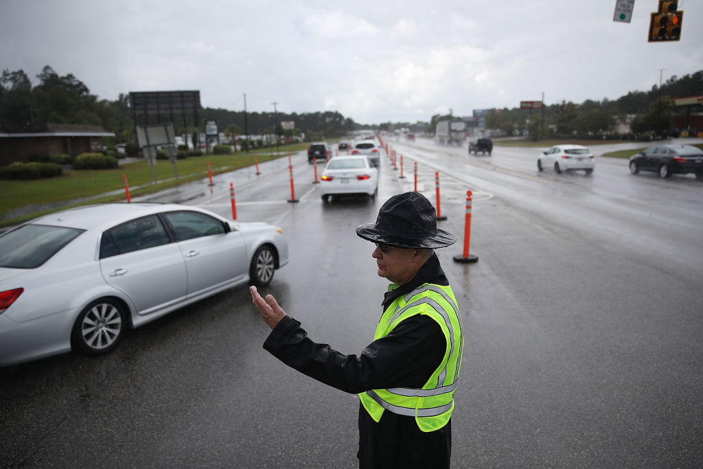 Jack Ross from the South Carolina Highway Patrol directs traffic onto US 501 as the South Carolina government ordered that traffic use all the lanes on the route leading away from the coast to facilitate the evacuation of people ahead of the arrival of Hurricane Florence on Sept. 11, 2018 in Myrtle Beach.