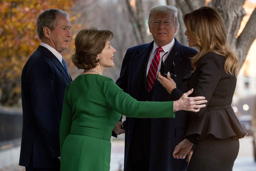 President Donald Trump and first lady Melania Trump are greeted by former President George Bush and former first lady Laura Bush outside the Blair House across the street from the White House in Washington, Tuesday, Dec. 4, 2018