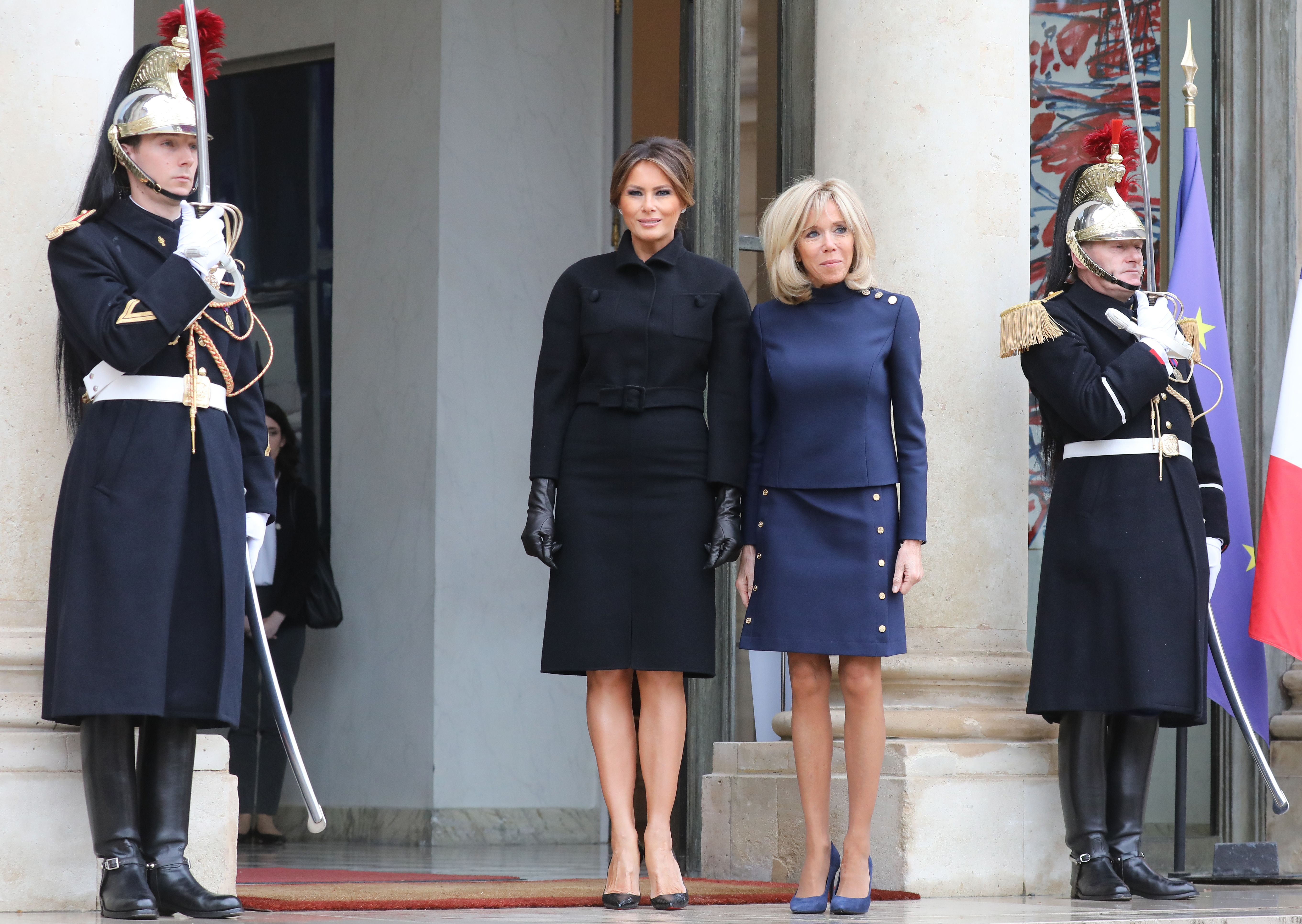 Melania Trump and Brigitte Macron stand side-by-side before entering the Elysee Palace.