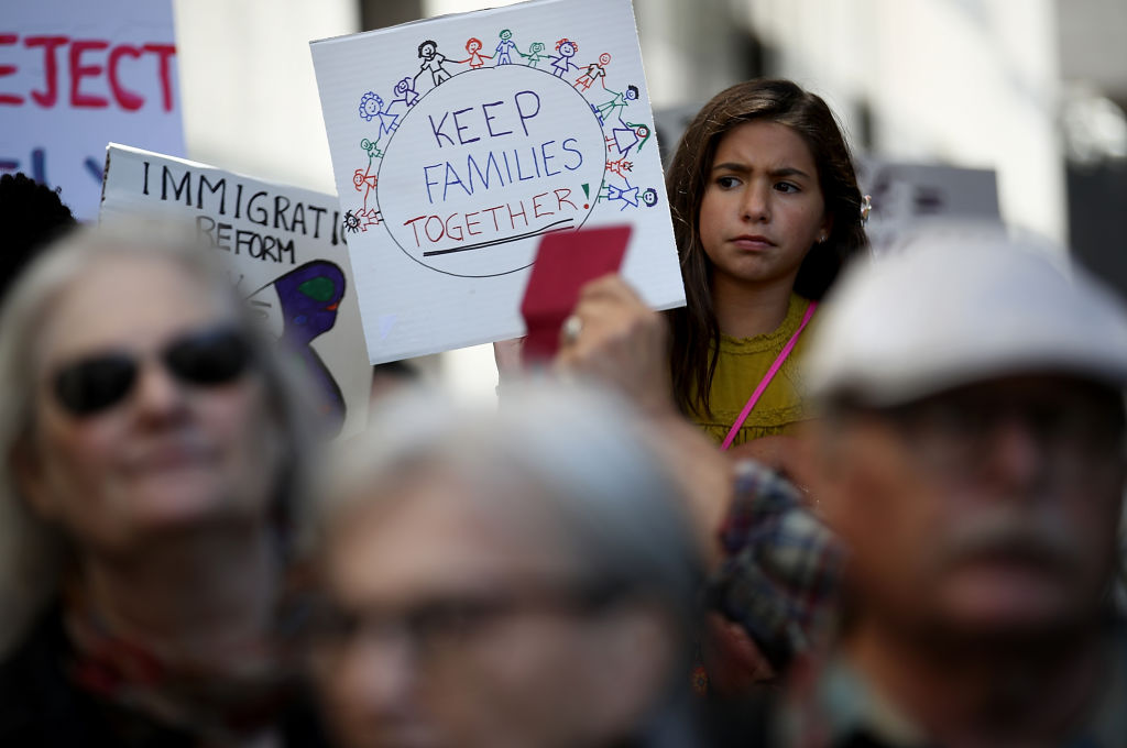 A young girl holds a sign during a demonstration outside of the San Francisco office of the Immigration and Customs Enforcement (ICE) on June 19, 2018 in San Francisco, California.