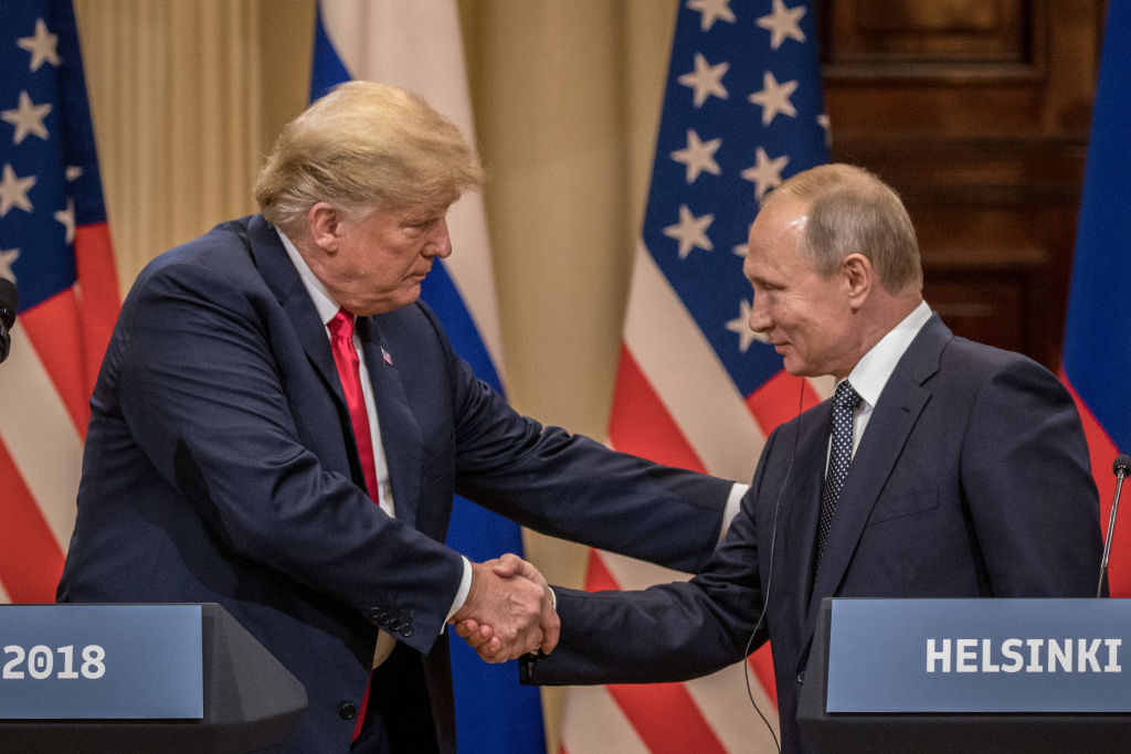 President Donald Trump (L) and Russian President Vladimir Putin shake hands during a joint press conference after their summit on July 16, 2018 in Helsinki, Finland.