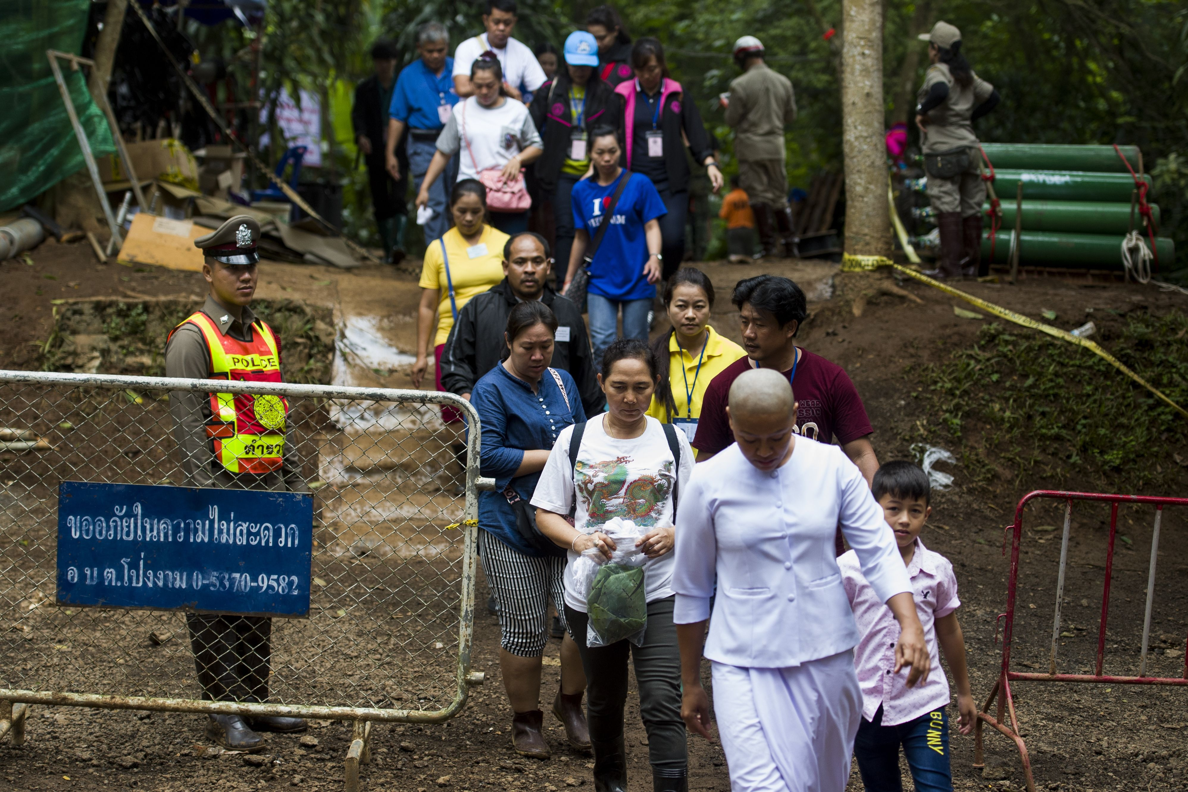 Relatives of the boys walk from the cave complex after taking part in a prayer ceremony as rescue operations continue for the 12 boys and their soccer coach.