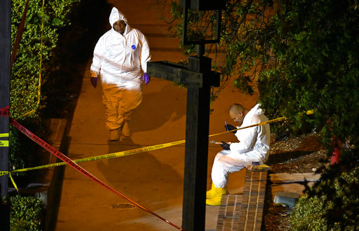 A forensics team works the scene Thursday, Nov. 8, 2018, in Thousand Oaks, California, where a gunman opened fire inside a bar crowded.