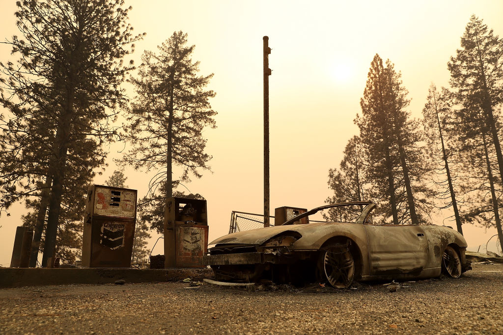 A burned out car sits next gas pumps at a gas station that was destroyed by the Camp Fire on Nov. 11, 2018 near Parkhill, California.