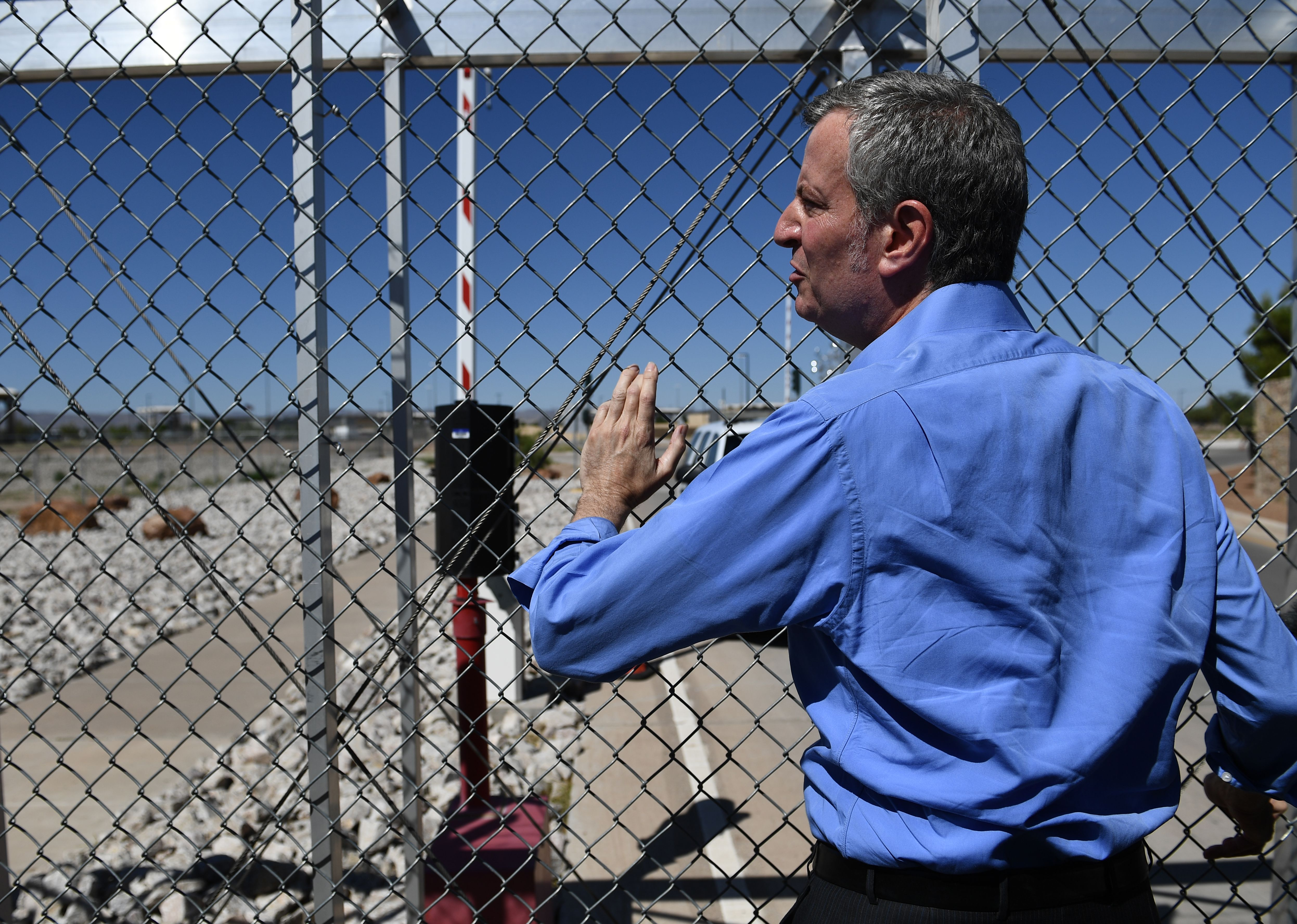 New York mayor Bill de Blasio stands at a fence of the Tornillo Port of Entry near El Paso, Texas, Thursday during a protest rally.