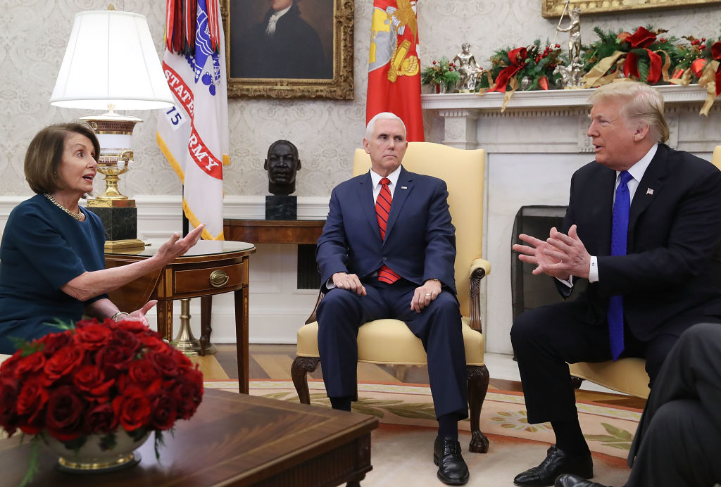President Donald Trump (R) argues about border security with House Minority Leader Nancy Pelosi (D-CA) as Vice President Mike Pence (C) sits nearby in the Oval Office on Dec. 11, 2018 in Washington, DC.