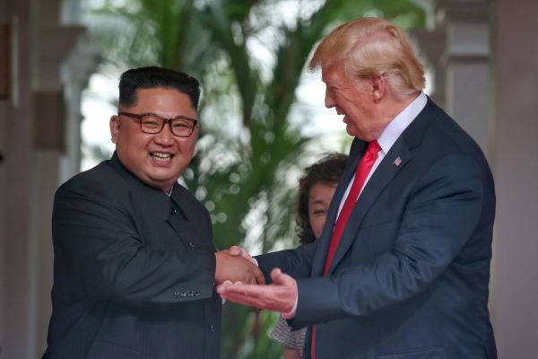 In this handout photo, North Korean leader Kim Jong-un shakes hands with President Donald Trump during their historic U.S.-DPRK summit at the Capella Hotel on Sentosa island on June 12, 2018 in Singapore.