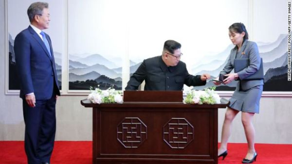 Kim Jong Un prepares to sign the guest book ahead of his meeting with South Korean President Moon Jae-in.