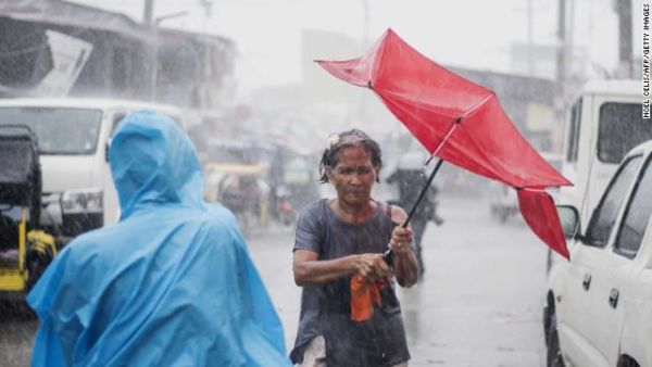 A woman holds her umbrella against the heavy rains pounding Manila on Saturday.