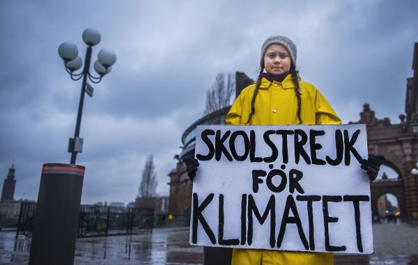 "Greta Thunberg holds a placard reading ""School strike for the climate"" during a protest outside the Swedish parliament on November 30, 2018."