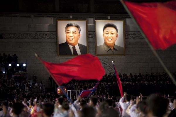 North Koreans wave flags in front of portraits of North Korean late president Kim Il-Sung (l.) and his son Kim Jung-Il.