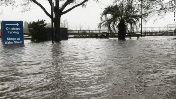 An area in downtown Wilmington, North Carolina, usually meant for street parking and relaxing on park benches is inundated by water from the swollen Cape Fear River.