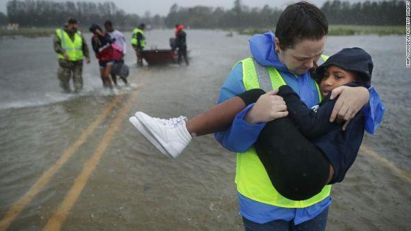 Volunteers from the Civilian Crisis Response Team help rescue three children from their flooded home in James City, North Carolina.