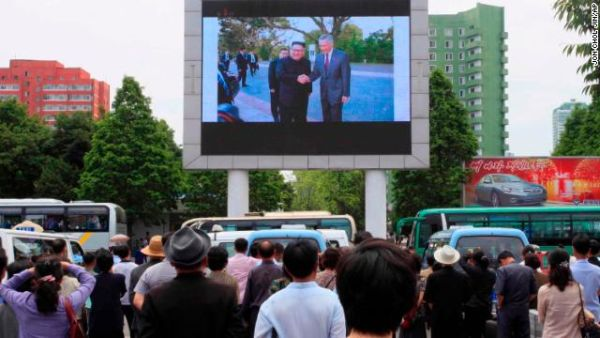 People watch a large screen at the main train station in Pyongyang, airing video of North Korean leader Kim Jong Un shaking hands with Singapore Prime Minister Lee Hsien Loong on June 11.