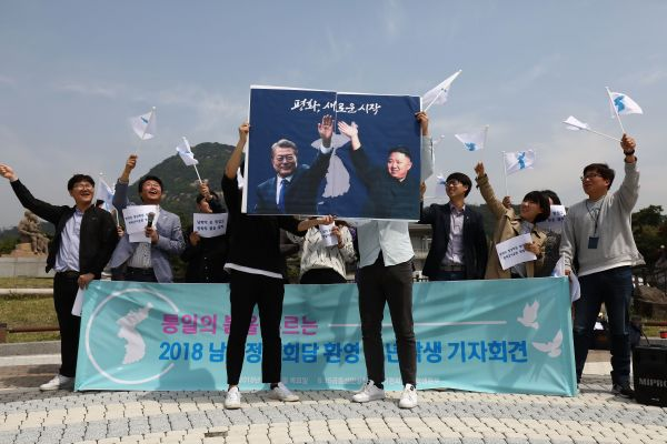 South Koreans hold up placards of Moon and Kim during a rally in front of the Presidential Blue House on Thursday in Seoul.
