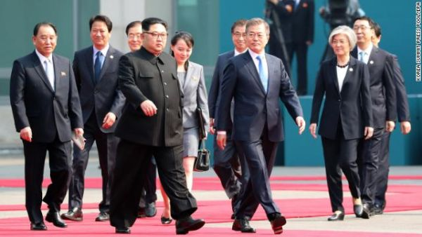 South Korean President Moon Jae-in (center right) and North Korean leader Kim Jong Un (center left) walk together with members of their delegations.