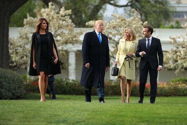 US first lady Melania Trump, US President Donald Trump, Brigitte Macron and French President Emmanuel Macron walk across the South Lawn before participating in a tree-planting ceremony at the White House April 23, 2018 in Washington, DC.