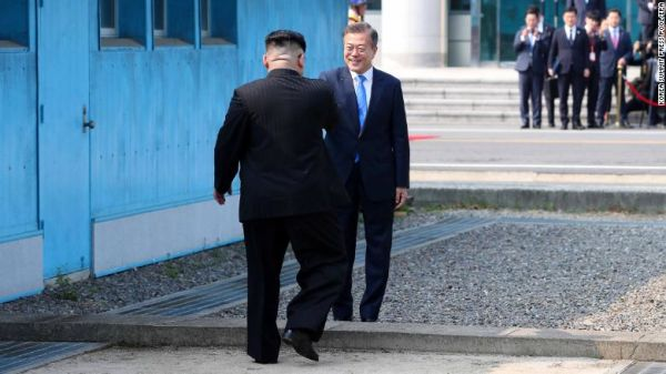 South Korean President Moon Jae-in and North Korean leader Kim Jong Un shake hands at the military demarcation line.