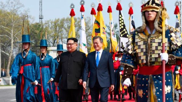 North Korean leader Kim Jong Un, left, and South Korean President Moon Jae-in walk together after he crossed into the southern side of the DMZ.