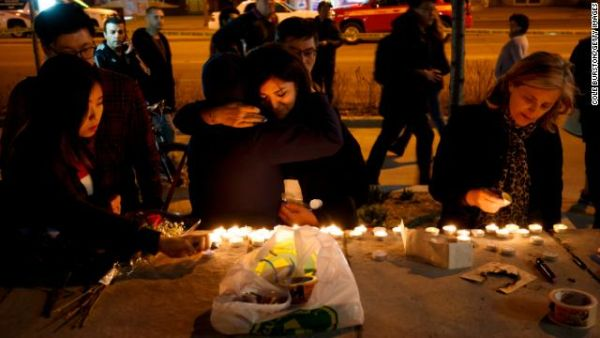 People embrace as they lay candles and leave messages at a memorial for victims of a crash on Yonge St. at Finch Ave., after a van plowed into pedestrians on April 23, 2018 in Toronto, Canada.