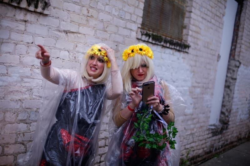 Sarah Myers, left, and Katie Voorhies look for their assigned bus to travel from the Krewe of Muses pre-party to the start of the parade. Credit: Kathleen Flynn for CNN