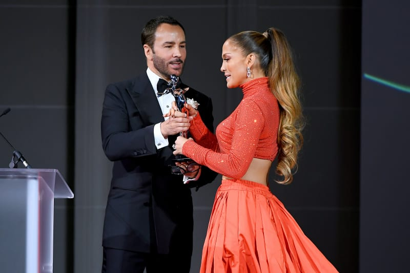 Jennifer Lopez and Tom Ford appear onstage at the CFDA Fashion Awards.