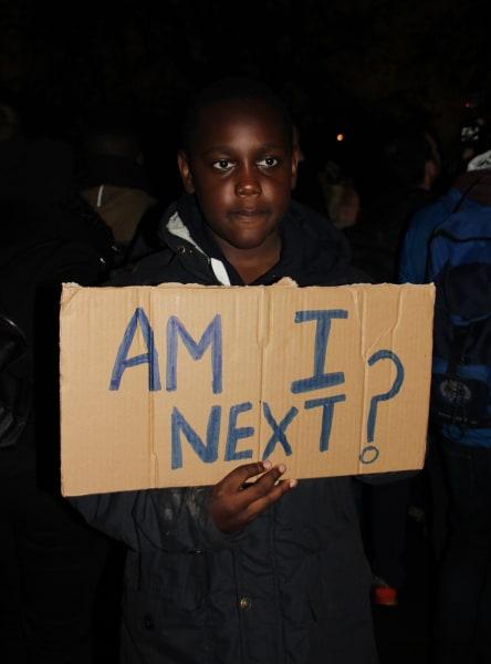 Protester London to Ferguson Am I Next sign