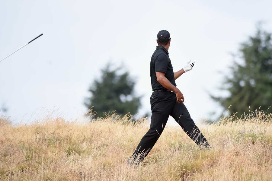 Tiger Woods throws club