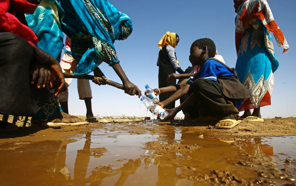 Sudanese woman fills boy's bottle drought