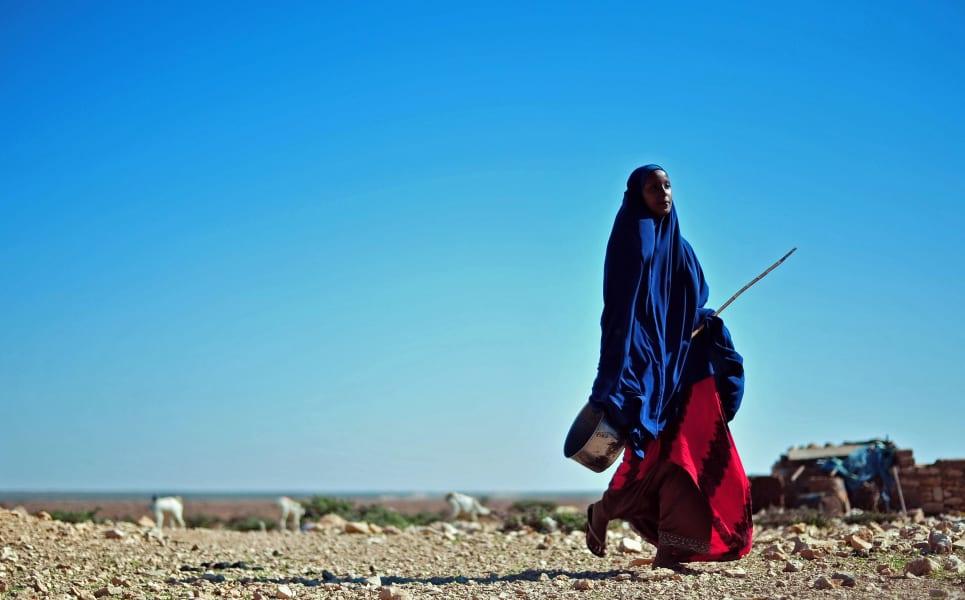 Somalian Woman walks through dryland