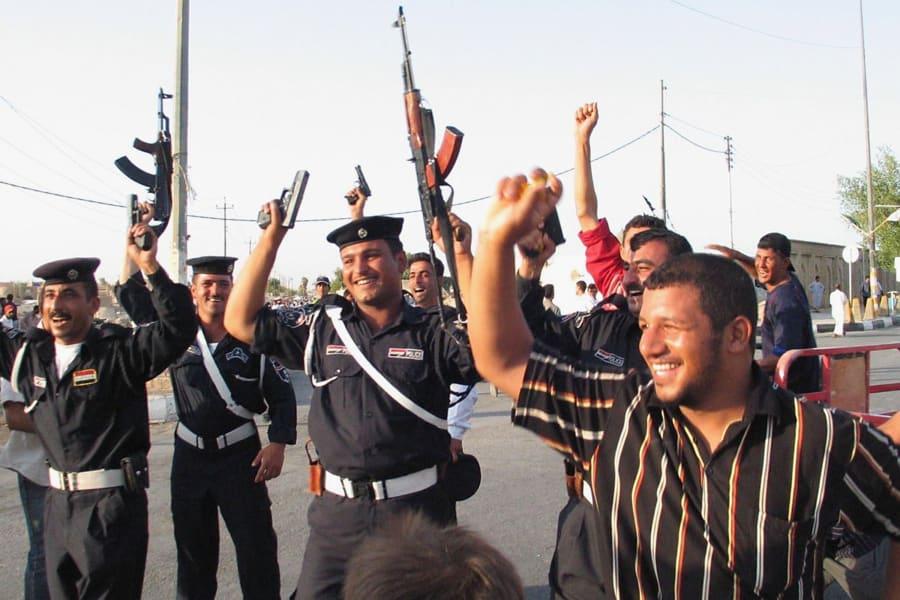 Iraqi police celebrate football guns