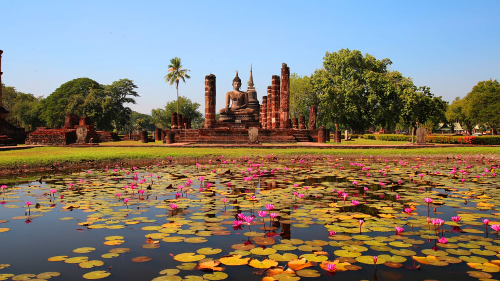 Buddha Statue behind water body with lily pads