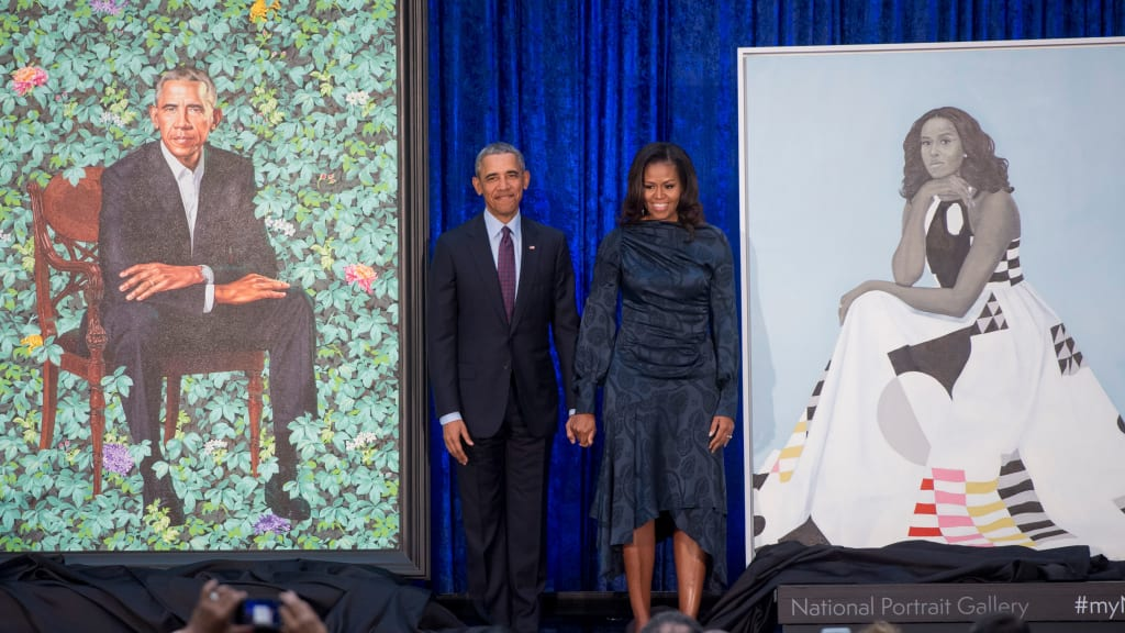 Former US President Barack Obama And First Lady Michelle Stand Beside Their Portraits After