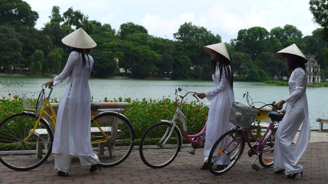 "Young girls wear traditional conical hats and ""ao dai"" dresses in honor of a celebration at Hoan Kiem Lake, a popular hangout for locals."