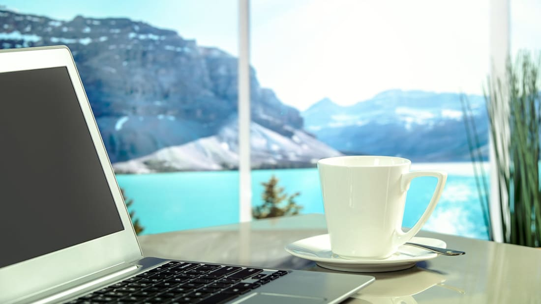 A laptop and a cup of tea or coffee, with view of mountain or lake beyond