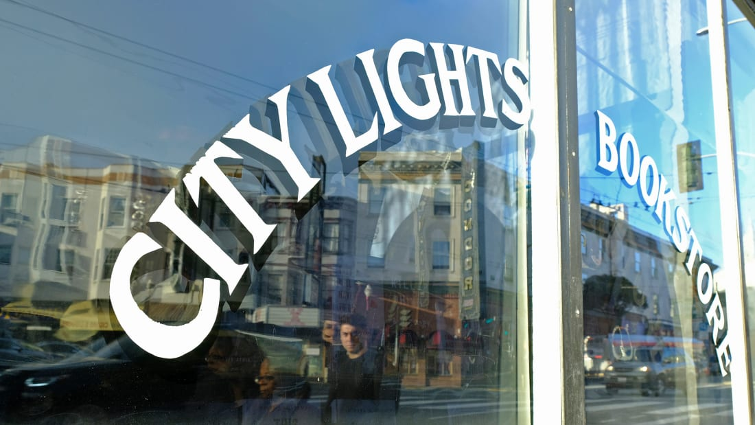 People are reflected in the window of the City Lights Bookstore in North Beach as they walk along Columbus Avenue, Friday, March 13, 2020, in San Francisco. A wave of closures and postponements spanning everything from government offices to cultural events and sports followed California Gov. Gavin Newsom's call this week for cancellation of all non-essential gatherings of 250 people or more because of the coronavirus threat. The vast majority of people recover from the new coronavirus. According to the World Health Organization, most people recover in about two to six weeks, depending on the severity of the illness. (AP Photo/Eric Risberg)