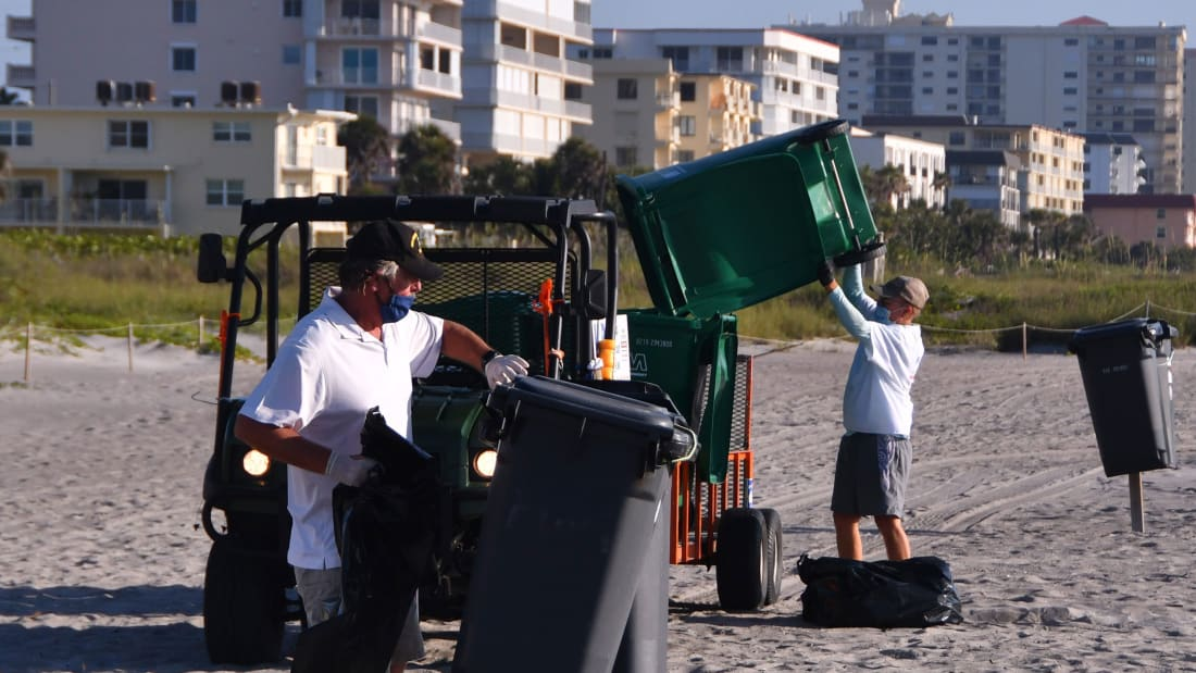 Keep Brevard Beautiful empties trash cans near Minutemen Causeway on May 9. KBB is running double shifts in some beachside areas to keep up with the litter and trash. Police and beach rangers are stepping up their litter monitoring.