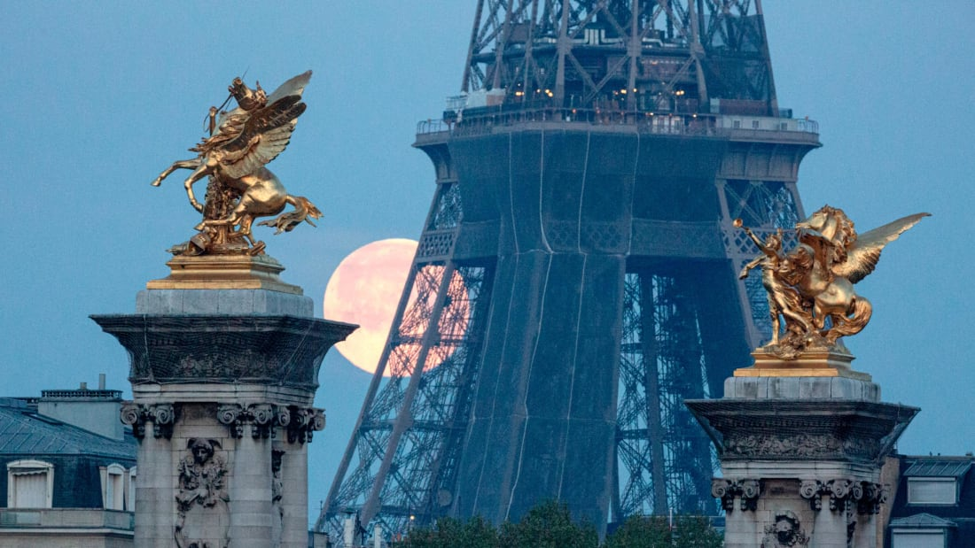 A supermoon sets behind the Eiffel Tower and statues of Pegasus Held By Fame on the Pont Alexandre III bridge in Paris on April 27, 2021.